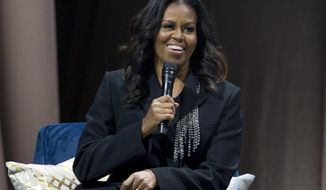 """Former first lady Michelle Obama speaks to the crowd as she presents her anticipated memoir """"Becoming"""" during her book tour stop in Washington, Saturday, Nov. 17, 2018. (AP Photo/Jose Luis Magana)"""