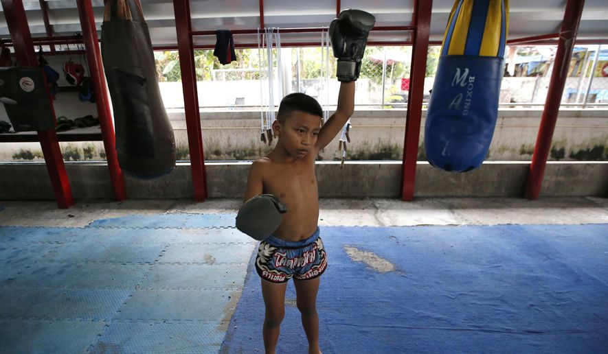 In this Wednesday, Nov. 14, 2018, photo, Thai kickboxer Chaichana Saengngern, 10-years old, warms up at a training camp in Bangkok, Thailand. Thai lawmakers recently suggested barring children younger than 12 from competitive boxing, but boxing enthusiasts strongly oppose the change. They say the sport is part of Thai culture and gives poor families the opportunity to raise a champion that will lift their economic circumstances. (AP Photo/Sakchai Lalit)