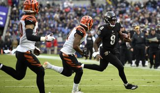 Baltimore Ravens quarterback Lamar Jackson (8) rushes the ball against Cincinnati Bengals defensive back Darqueze Dennard, center, and free safety Jessie Bates in the first half of an NFL football game, Sunday, Nov. 18, 2018, in Baltimore. (AP Photo/Nick Wass)
