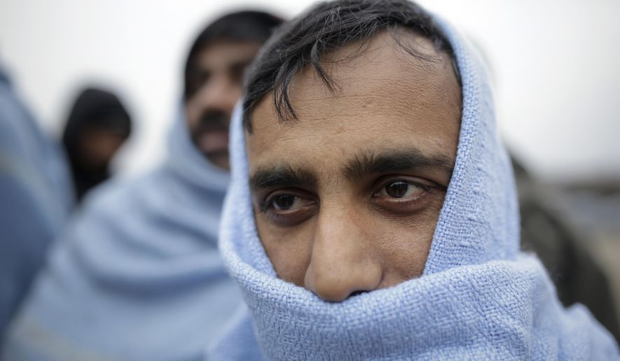 In this Sunday, Nov. 18, 2019 photo a migrant wrapped in a blanket waits for food distribution at a camp in Velika Kladusa, Bosnia, close to the border to Croatia. The approach of the tough Balkan winter spells tough times for the migrants that remain stuck in the region while trying to reach Western Europe, with hundreds of them staying in make-shift camps with no heating or facilities.(AP Photo/Amel Emric)