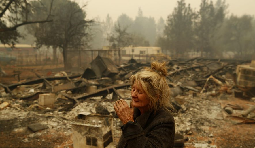 "FILE - In this Nov. 9, 2018 photo, Cathy Fallon reacts as she stands near the charred remains of her home in Paradise, Calif. ""I'll be darned if I'm gonna let those horses burn in the fire"" said Fallon, who stayed on her property to protect her 14 horses, ""It has to be true love."" (AP Photo/John Locher, File)"