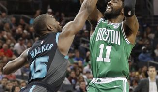 Boston Celtics' Kyrie Irving (11) shoots over Charlotte Hornets' Kemba Walker (15) during the first half of an NBA basketball game in Charlotte, N.C., Monday, Nov. 19, 2018. (AP Photo/Chuck Burton)
