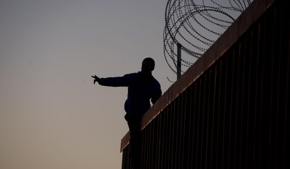 A Mexican citizen gestures after climbing the border fence to take pictures of himself, in Tijuana, Mexico, Sunday, Nov. 18, 2018. (AP Photo/Ramon Espinosa)