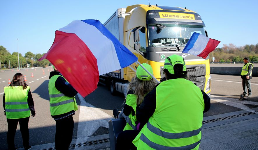 Demonstrators wearing yellow jackets open the toll gates on motorway at Benesse-Maremne southwestern France, Monday, Nov.19, 2018. The protests reflect broader frustration at President Emmanuel Macron, whose government is sticking to the fuel tax rise as part of efforts to clean up the environment. (AP Photo/Bob Edme)