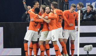 Netherland's Virgil Van Dijk is celebrated by his team after scoring his side's second goal in the 90th minute during the UEFA Nations League soccer match between Germany and The Netherlands in Gelsenkirchen, Monday, Nov. 19, 2018. The match ended 2-2. (AP Photo/Martin Meissner)
