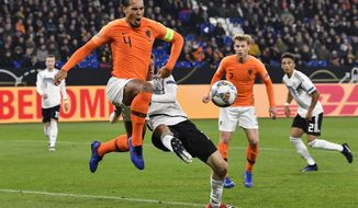 Netherland's Virgil Van Dijk, left, and Germany's Thomas Mueller challenge for the ball during the UEFA Nations League soccer match between Germany and The Netherlands in Gelsenkirchen, Monday, Nov. 19, 2018. (AP Photo/Martin Meissner)