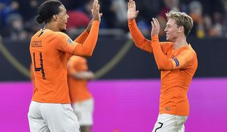 Netherland's Virgil Van Dijk, left, and Netherland's Frenkie De Jong celebrate after the UEFA Nations League soccer match between Germany and The Netherlands in Gelsenkirchen, Monday, Nov. 19, 2018. The match ended 2-2. (AP Photo/Martin Meissner)