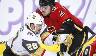 Vegas Golden Knights' William Carrier, left, checks Calgary Flames' Rasmus Andersson, of Sweden, during first-period NHL hockey game action in Calgary, Alberta, Monday, Nov. 19, 2018. (Jeff McIntosh/The Canadian Press via AP)