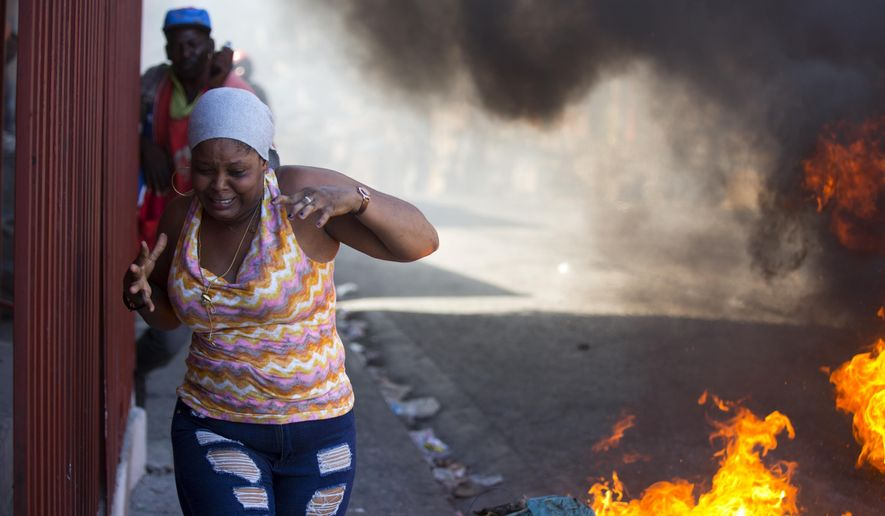 Residents run past burning barricades during a strike that is part of protests demanding to know how Petro Caribe funds have been used by the current and past administrations, in Port-au-Prince, Haiti, Monday, Nov. 19, 2018. Much of the financial support to help Haiti rebuild after the 2010 earthquake comes from Venezuela's Petro Caribe fund, a 2005 pact that gives suppliers below-market financing for oil and is under the control of the central government. (AP Photo/Dieu Nalio Chery)