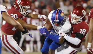 Kansas running back Pooka Williams Jr., center, is tackled by Oklahoma safety Robert Barnes, left, and linebacker Curtis Bolton, right, during the first half of an NCAA college football game in Norman, Okla., Saturday, Nov. 17, 2018. (AP Photo/Alonzo Adams)