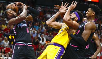 Miami Heat guard Josh Richardson, left, Los Angeles Lakers center JaVale McGee, center, and Heat center Hassan Whiteside are unable to come up with a rebound during the first half of an NBA basketball game, Sunday, Nov. 18, 2018, in Miami. (AP Photo/Brynn Anderson)