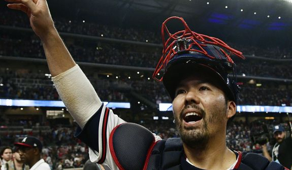 FILE - In this Oct. 7, 2018, file photo, Atlanta Braves catcher Kurt Suzuki celebrates after Game 3 of baseball's National League Division Series against the Los Angeles Dodgers, in Atlanta. Catcher Kurt Suzuki is heading back to the Washington Nationals after agreeing to a $10 million, two-year contract, a deal pending a successful physical. The deal was disclosed to The Associated Press on Monday, Nov. 19, 2018, by a person familiar with the agreement who spoke on condition of anonymity because the contract was not yet official. (AP Photo/John Amis, File) **FILE**