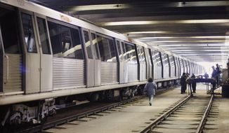FILE - In this Nov. 17, 2009 file photo, subway workers walk by a parked train in Bucharest, Romania. The Bucharest subway union said on Monday, Nov. 19, 2018, that subway workers in the Romanian capital will go on strike this week after they failed to win an agreement on wage demands. (AP Photo/Vadim Ghirda, File)