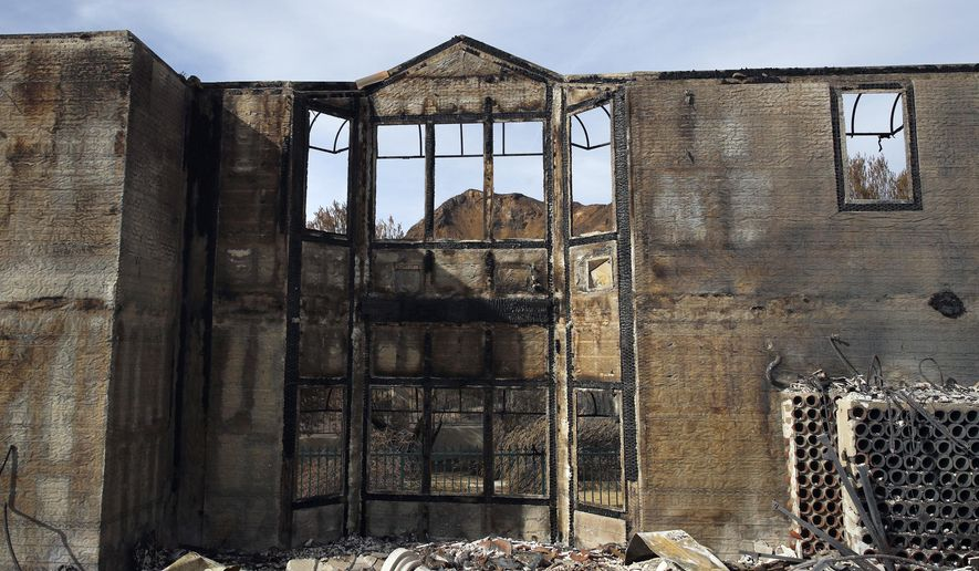 FILE - This Nov. 13, 2018 file photo shows the charred window frames of a mansion destroyed by the Woolsey fire in Agoura Hills, Calif. The number of structures destroyed by a huge Southern California wildfire has risen to 1,500. Another 341 structures were damaged as of a Monday, Nov. 20, 2018 count. As firefighters mop up, repair and restoration of utilities is continuing along with repopulation of areas. (AP Photo/Jae C. Hong)