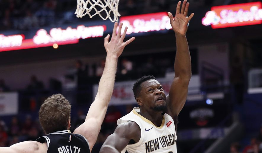 New Orleans Pelicans forward Julius Randle (30) shoots against San Antonio Spurs center Jakob Poeltl (25) in the first half of an NBA basketball game in New Orleans, Monday, Nov. 19, 2018. (AP Photo/Gerald Herbert)