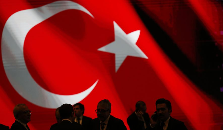 Backdropped by Turkey's flag officials wait for an event to be attended by Turkey's President Recep Tayyip Erdogan and Russian President Vladimir Putin, marking the completion of one of the phases of the Turkish Stream natural gas pipeline, in Istanbul, Monday, Nov. 19, 2018.  The two 930-kilometer (578-mile) lines when finished are expected to carry 31.5 billion cubic meters (1.1 trillion cubic feet) of Russian natural gas annually to European markets, through Turkish territories.(AP Photo/Lefteris Pitarakis)