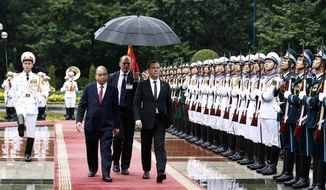 Russian Prime Minister Dmitry Medvedev, center right, and his Vietnamese counterpart Nguyen Xuan Phuc review an honor guard in Hanoi, Vietnam, Monday, Nov. 19, 2018. Medvedev is in Vietnam for a two-day visit to boost ties between the two countries. (Hoang Thong Nhat/Vietnam News Agency via AP)