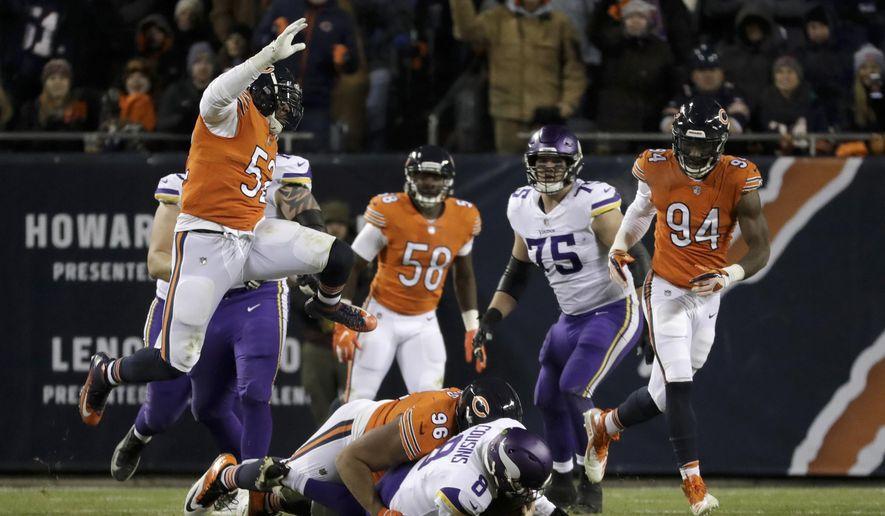 Chicago Bears linebacker Khalil Mack (52) leaps over as Bears defensive end Akiem Hicks (96) sacks Minnesota Vikings quarterback Kirk Cousins (8) during the second half of an NFL football game Sunday, Nov. 18, 2018, in Chicago. (AP Photo/Nam Y. Huh)