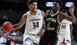 Cincinnati's Jarron Cumberland (34) drives against Western Michigan Adrian Martin (2) during the first half of an NCAA college basketball game, Monday, Nov. 19, 2018, in Cincinnati. (AP Photo/John Minchillo)