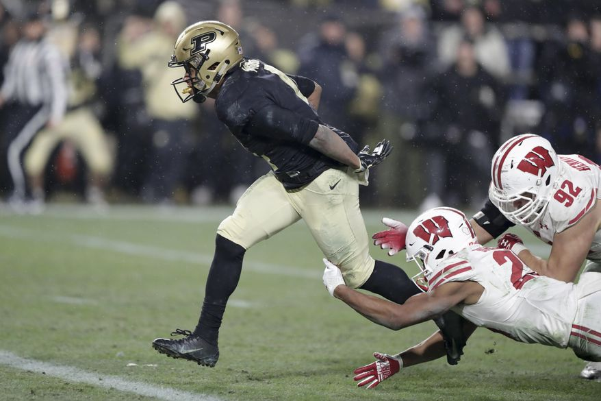 Purdue wide receiver Rondale Moore (4) breaks the tackle of Wisconsin defensive end Matt Henningsen (92) and safety Eric Burrell (25) on his way to a touchdown during overtime of an NCAA college football game in West Lafayette, Ind., Saturday, Nov. 17, 2018. Wisconsin defeated Purdue 47-44 in overtime. (AP Photo/Michael Conroy)