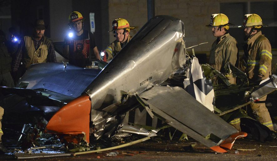 In this Saturday, Nov. 17, 2018, photo firefighters and investigators look over a vintage World War II P-51D Mustang aircraft after a deadly crash in Fredericksburg, Texas. (Billy Calzada/The San Antonio Express-News via AP)