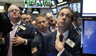 In this Wednesday, Nov. 14, 2018, file photo Dudley Devine, right, works with fellow traders on the floor of the New York Stock Exchange. On Tuesday, Nov. 20, stocks are opening sharply lower on Wall Street as a rout in major technology companies continued. (AP Photo/Richard Drew, File)