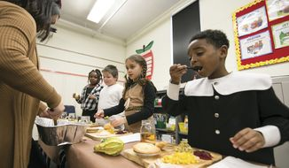 Second-grader KaMari Washington, right, enjoys a Thanksgiving meal with his classmates in Mitzi Collins classroom at Clark Elementary in Paducah, Ky. on Tuesday, Nov. 20, 2018. Parents provided traditional Thanksgiving dishes and the students were encouraged to dress as Native Americans or Pilgrims. (Ellen O'Nan/The Paducah Sun via AP) ** FILE **
