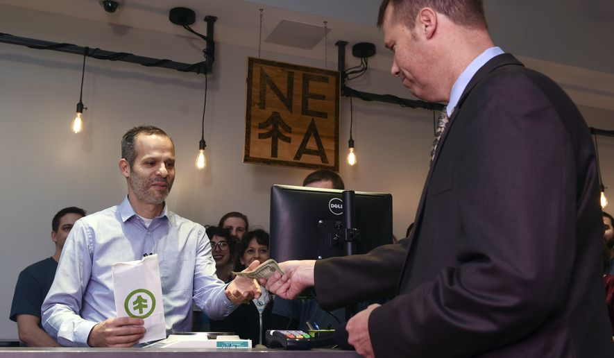NETA co-founder Arnon Vered sells Northampton Mayor David Narkewicz, right, the first legal recreational sale of marijuana, an edible marijuana candy bar, at the NETA facility on Tuesday, Nov. 20, 2018, in Northampton, Mass. The state's first commercial pot shops opened Tuesday in Leicester and Northampton. The stores are the first to operate on the East Coast of the U.S., and there were long lines at both locations. (Carol Lollis/The Daily Hampshire Gazette via AP)