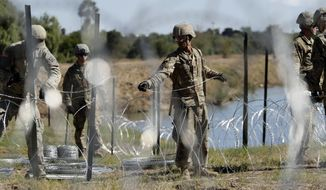 In this Nov. 16, 2018, photo, members of the U.S. military install multiple tiers of concertina wire along the banks of the Rio Grande near the Juarez-Lincoln Bridge at the U.S.-Mexico border in Laredo, Texas. The Pentagon is estimating the cost of the military's mission on the U.S.-Mexico border will be about $210 million under current plans. (AP Photo/Eric Gay)