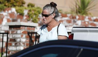 FILE - In this Thursday, Nov. 8, 2018, file photo, Colleen Long, mother of shooting suspect David Ian Long, leaves her house in Newbury Park, Calif. If authorities have concluded why Ian David Long shot and killed 12 people at a Southern California bar, they aren't sharing, and his family isn't talking, either. That has left a community still in mourning to wonder why, but also ask who was the man who shattered the sense of security in the Los Angeles suburb of Thousand Oaks? (AP Photo/Jae C. Hong, File)