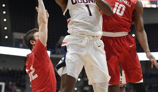 Connecticut's Christian Vital (1) shoots as Cornell's Jack Gordon (32) and Matt Morgan (10) defend during the first half of an NCAA college basketball game, Tuesday, Nov. 20, 2018, in Hartford, Conn. (AP Photo/Jessica Hill)