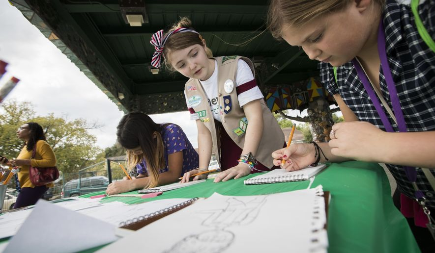 "Izzy Plunkett, 13, a Girl Scouts Troop 14527 Cadette, helps Girl Scouts Valentina Urteaga, left, 9, and Grace Eppley, 10, right, learn how to draw, Saturday, Nov. 17, 2018, in Houston. Plunkett organized an event titled ""Recovery Through Art,"" focused on teaching other girls techniques to recover from traumatic events by expressing themselves through the arts. (Marie D. De Jesus/Houston Chronicle via AP) ** FILE **"
