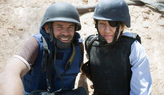 This image released by Arrow Media shows photographer Paul Conroy, left, with war correspondent Marie Colvin in Misrata, Libya. A new documentary recounts in searing detail the final days of Colvin, who was killed in shelling from Syrian President Bashar Assad's forces in 2012 in the city of Homs, where she was documenting civilian suffering. (Paul Conroy/Arrow Media via AP)
