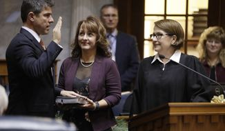 Sen. Rodric Bray, R-Martinsville, takes the oath of office from Judge Loretta Rush as his wife, Kelly, holds the Bible during organization day at the Statehouse, Tuesday, Nov. 20, 2018, in Indianapolis. Bray was selected to replace outgoing President Pro Temp David Long. (AP Photo/Darron Cummings)