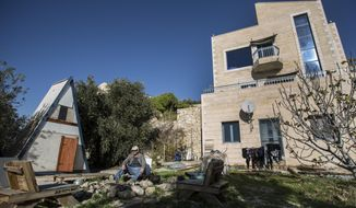 FILE - In this Jan. 17, 2016 file photo, Moshe Gordon sits outside his guest house advertised on the Airbnb international home-sharing site, in the Nofei Prat settlement in the West Bank. On Tuesday, Nov. 20, 2018, Israel's Tourism Minister Yariv Levin threatened the vacation rental company Airbnb with higher taxes, restrictions and legal repercussions over its decision to remove listings from Israeli settlements in the West Bank. (AP Photo/Tsafrir Abayov, File)