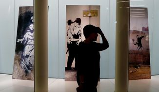 """A person admires a preview of the """"A Visual Protest. The Art of Banksy"""" exhibition dedicated to British artist Banksy, in Milan, Italy, Tuesday, Nov. 20, 2018. The exhibition will open to visitors Nov. 21, 2018 through to April 14, 2019.  (AP Photo/Antonio Calanni)"""