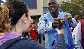 Charlotte Hornets owner Michael Jordan greets people and hands out food for Thanksgiving to members of the community in Wilmington, N.C., Tuesday, Nov. 20, 2018. (AP Photo/Gerry Broome)