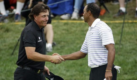 FILE - In this Aug. 8, 2014, file photo, Phil Mickelson, left, shakes hands with Tiger Wood after the second round of the PGA Championship golf tournament at Valhalla Golf Club in Louisville, Ky. Woods and Mickelson play pay-per-view exhibition Friday in Las Vegas. (AP Photo/David J. Phillip, File) **FILE**