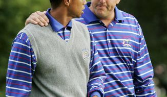 FILE - In this Sept. 17, 2004, file photo, U.S. team player Phil Mickelson puts his arm around partner Tiger Woods as they walk off the 18th green after they lost to Europeans Darren Clarke and Lee Westwood on the final hole of their foursomes match at the 35th Ryder Cup at Oakland Hills Country Club in Bloomfield Township, Mich. They play a high-stakes exhibition Friday in Las Vegas in golf's first venture using pay-per-view. (AP Photo/Dave Martin, File)