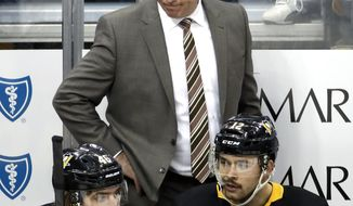 Pittsburgh Penguins head coach Mike Sullivan, top, stands behind Zach Aston-Reese (46) and Dominik Simon (12) during the third period of an NHL hockey game against the Buffalo Sabres in Pittsburgh, Monday, Nov. 19, 2018. (AP Photo/Gene J. Puskar)