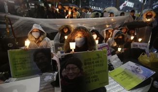FILE - In this Dec. 30, 2015 file photo, college students hold portraits of the deceased former South Korean sex slaves who were forced to serve for the Japanese military in World War II, and lit candles during a rally against Japanese government in front of the Japanese Embassy in Seoul, South Korea. South Korea says it will dissolve a foundation funded by Japan to compensate South Korean women who were forced to work in Japan's World War II military brothels. Seoul's Ministry of Gender Equality and Family said Wednesday, Nov. 21, 2018,  it will take legal steps to dissolve the foundation. (AP Photo/Ahn Young-joon, File)