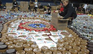"Cole Brekke, an eighth-grade student at Discovery Middle School in Fargo, N.D., packs up canned goods for the annual ""Fill The Dome"" food drive at the Fargodome indoor stadium on Tuesday, Nov. 20, 2018. This is the 12th year of the event and includes participation by high school, junior high and elementary schools from about 50 schools in the area. Officials say their efforts will provide about 300,000 meals for families in the region. (AP Photo/Dave Kolpack)"