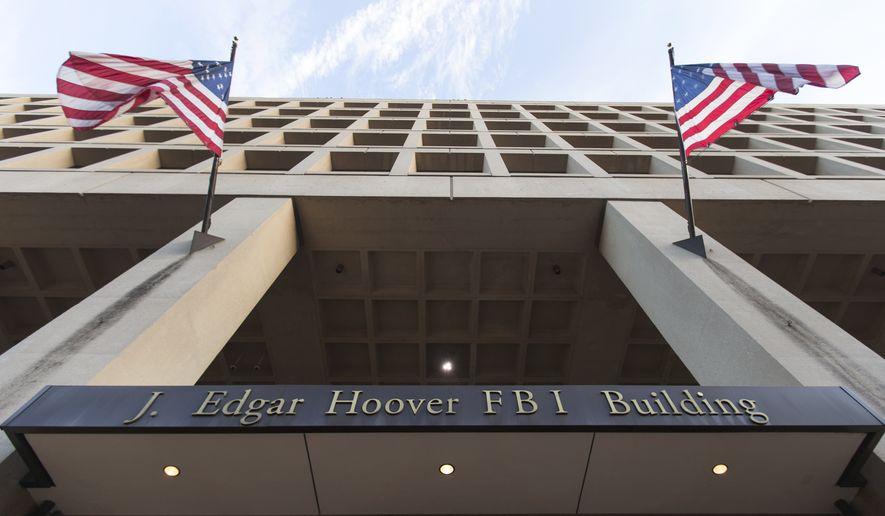The Pennsylvania Avenue entrance of the J. Edgar Hoover Federal Bureau of Investigations (FBI) Building is seen in Washington, Thursday, Nov. 30, 2017. (AP Photo/Carolyn Kaster/File)