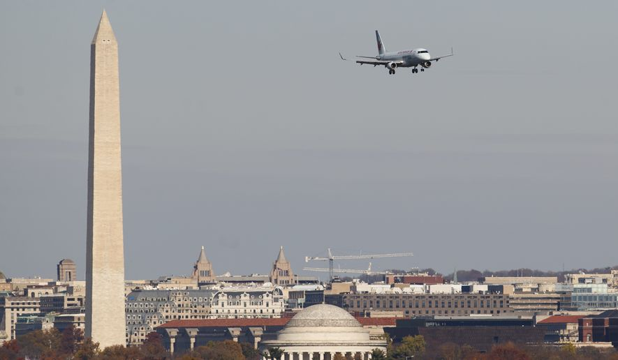 An airplane flies near the Washington Monument on approach to Washington Reagan National Airport, Wednesday, Nov. 21, 2018, in Arlington, Va. The airline industry trade group Airlines for America expects that Wednesday will be the second busiest day of the holiday period behind only Sunday, when many travelers will be returning home after Thanksgiving. (AP Photo/Carolyn Kaster)
