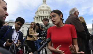 In this Nov. 14, 2018, file photo, Rep.-elect Alexandria Ocasio-Cortez, D-N.Y., talks with reporters following a photo opportunity on Capitol Hill in Washington, with the freshman class. (AP Photo/Susan Walsh, File)