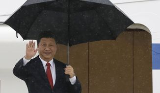 Chinese President Xi Jinping waves before he departs Manila's International Airport in Philippines during rain Wednesday, Nov. 21, 2018. Xi ended his two-day visit in the Philippines, his first visit to the U.S. treaty ally, with offers of infrastructure loans and new accords to prevent clashes and possibly explore for oil and gas in the disputed South China Sea. (AP Photo/Aaron Favila)