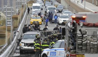 Police and fire officials investigate the scene of a fiery crash involving three vehicles on the Brooklyn Bridge, Wednesday morning, Nov. 21, 2018, in New York. Fire Department officials said six people were injured, and one person was killed.   (AP Photo/Bebeto Matthews)
