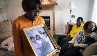Glenda O'Neal, mother of of Dr. Tamara O'Neal, shows a photo of her family at their home in LaPorte, Ind., Tuesday, Nov. 20, 2018. Dr. Tamara was one of the three people fatally shot Monday at Mercy Hospital, a Chicago hospital. (Zbigniew Bzdak/Chicago Tribune via AP)