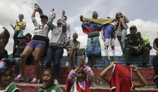 Venezuelan migrants celebrate a goal during a soccer match at their temporary camp in Bogota, Colombia, Wednesday, Nov. 21, 2018. City officials organized soccer matches for migrants living in the camp, built by the city's social welfare agency to accommodate migrants who had previously been living in tents made of plastic sheets and scrap materials outside the city's bus terminal. (AP Photo/Ivan Valencia)