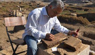 This undated photo released by the Egyptian Ministry of Antiquities, shows an archaeologist working on a block of limestone that was found in the temple of Ra, the ancient Egyptian god of the sun, in the Matariya neighborhood of Cairo, Egypt. The Antiquities Ministry said Wednesday, Nov. 21, 2018, that archaeologists digging in Cairo found two blocks of limestone with inscriptions belonging to an engineer who worked for Ramses II, one of the longest ruling pharaohs in antiquity. (Egyptian Ministry of Antiquities via AP)